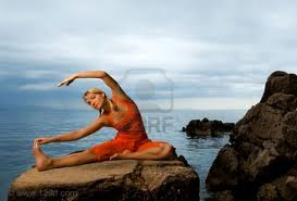 woman stretching on rock